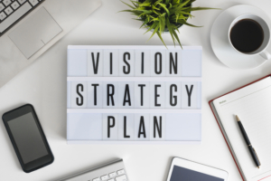 Vision, strategy and plan words on office table with computer, coffee, notepad, smartphone and digital tablet